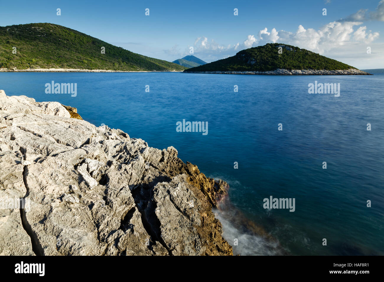 Morning over the rocky coastal area of Cunski with a view to the island of Veli Osir and Osorscica mountain in the Stock Photo