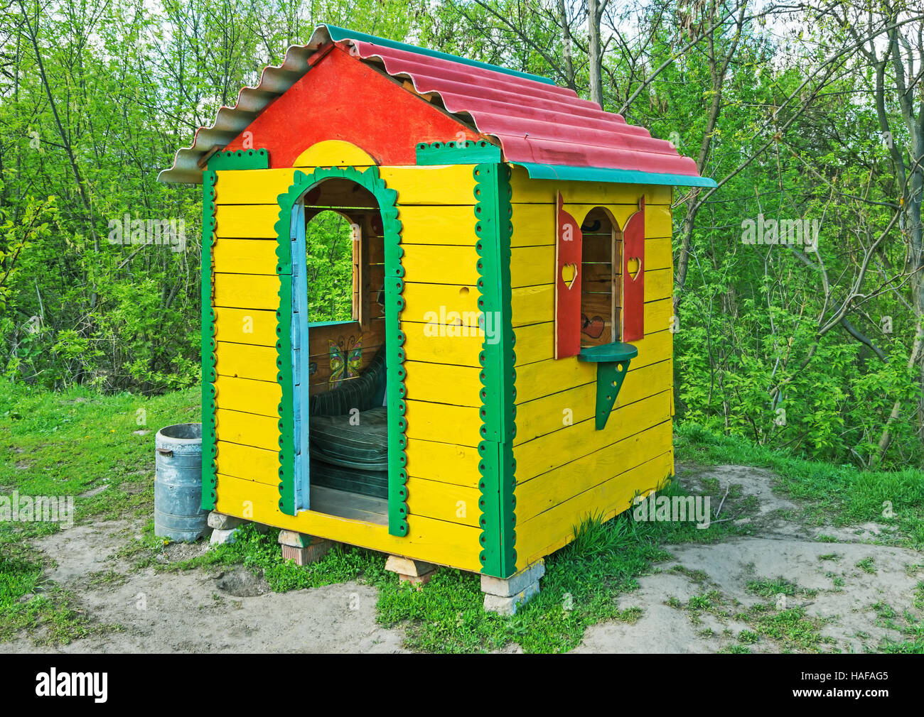 A small children's playhouse on the lawn in the city park in early spring - Stock Image
