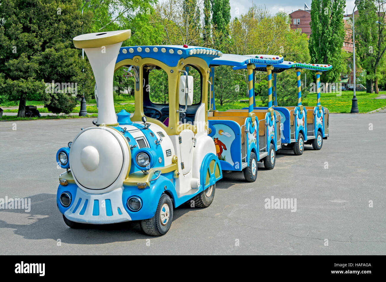 Cheerfully painted children's train for walks in the amusement park - Stock Image