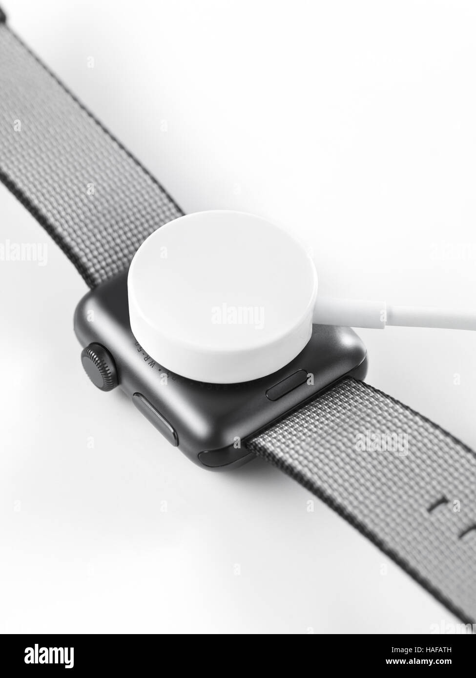 Apple Watch smartwatch charging wirelessly by inductive wireless charger - Stock Image