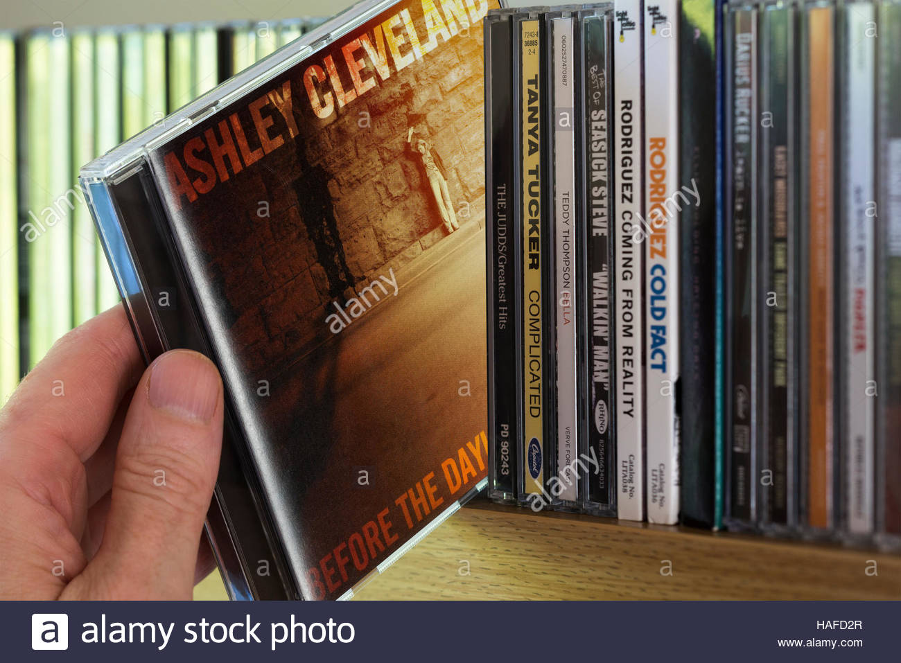 Before the Daylight's Shot, 2006 Ashley Cleveland CD being chosen from a shelf of other CD's - Stock Image
