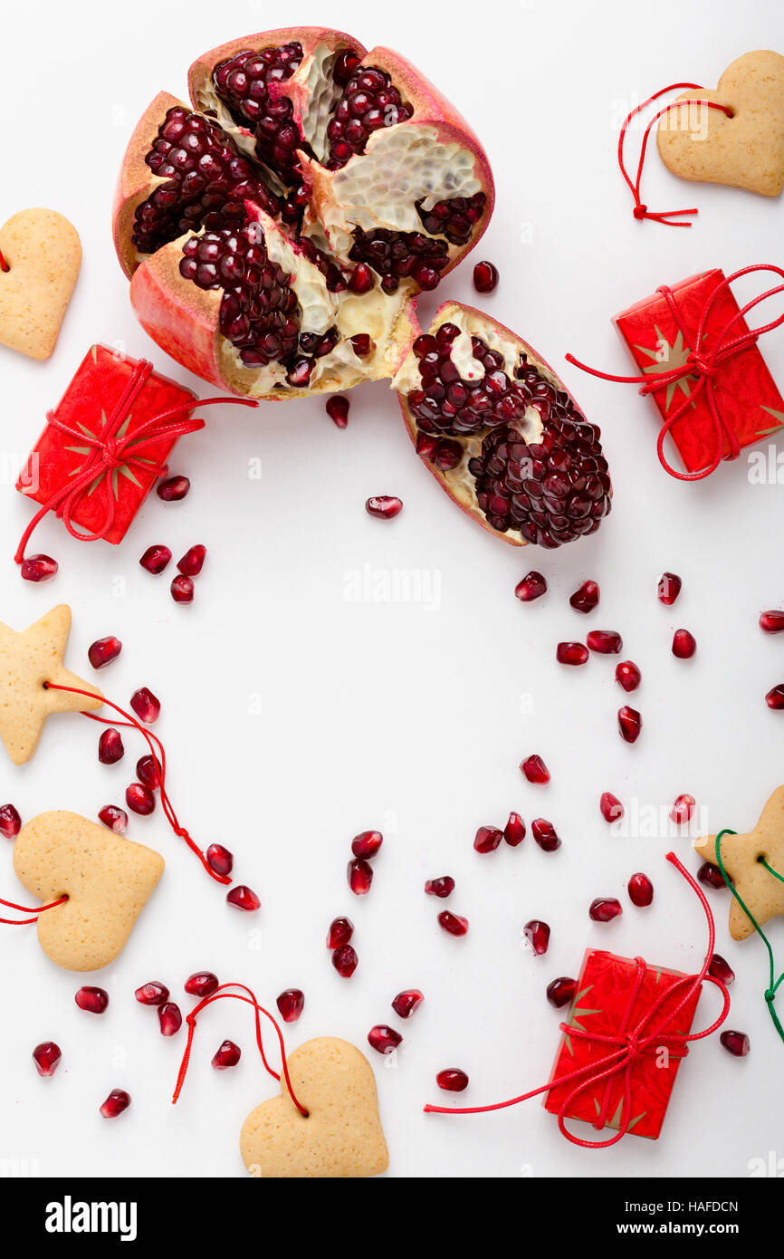 Frame of homemade christmas cookies, pomegranate seeds and gifts with copy spase for holiday text. Xmas handmade - Stock Image