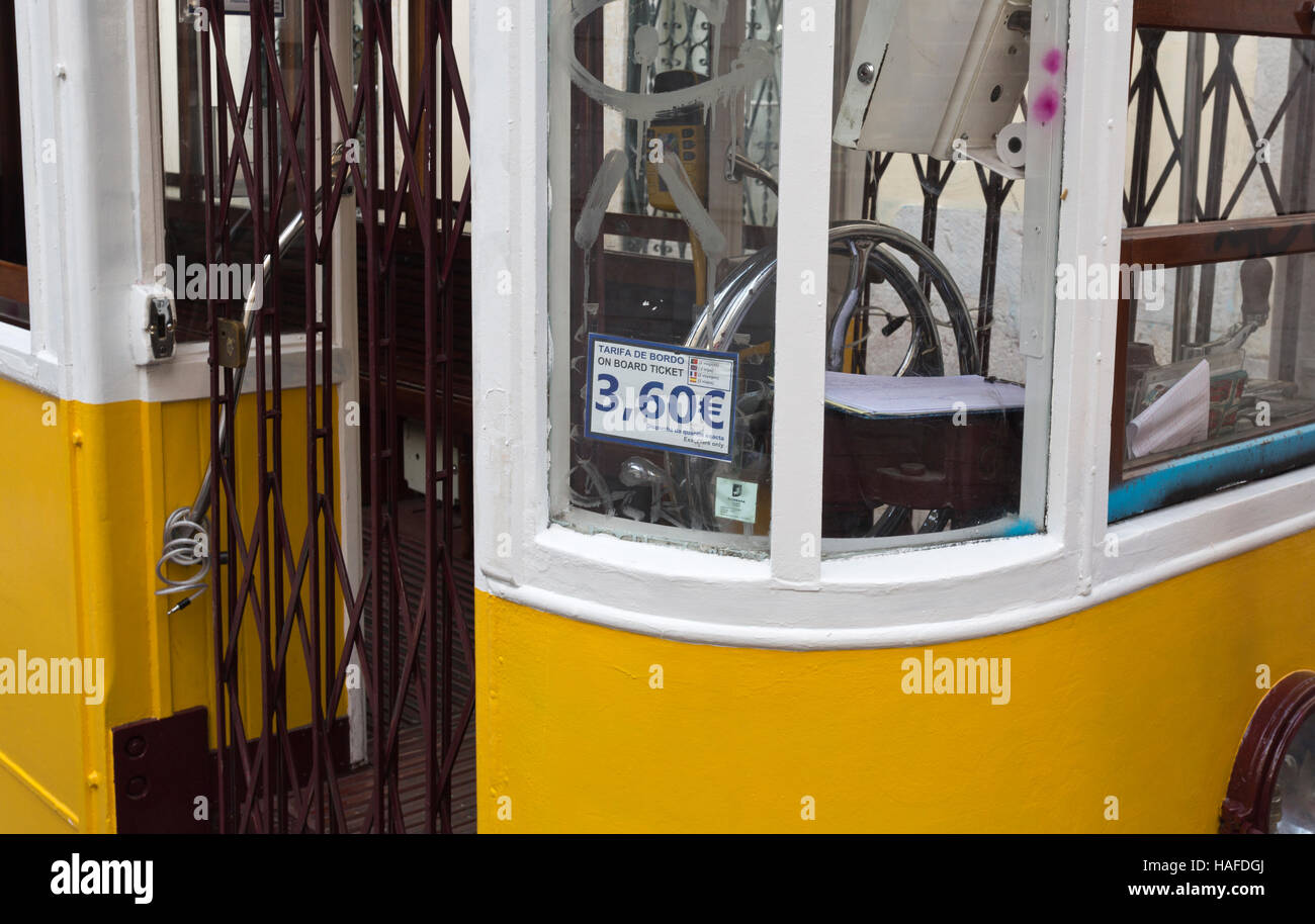 Detail of the tram entry, steering wheel and the exorbitant fare of a minute journey down the street in Lisbon, - Stock Image