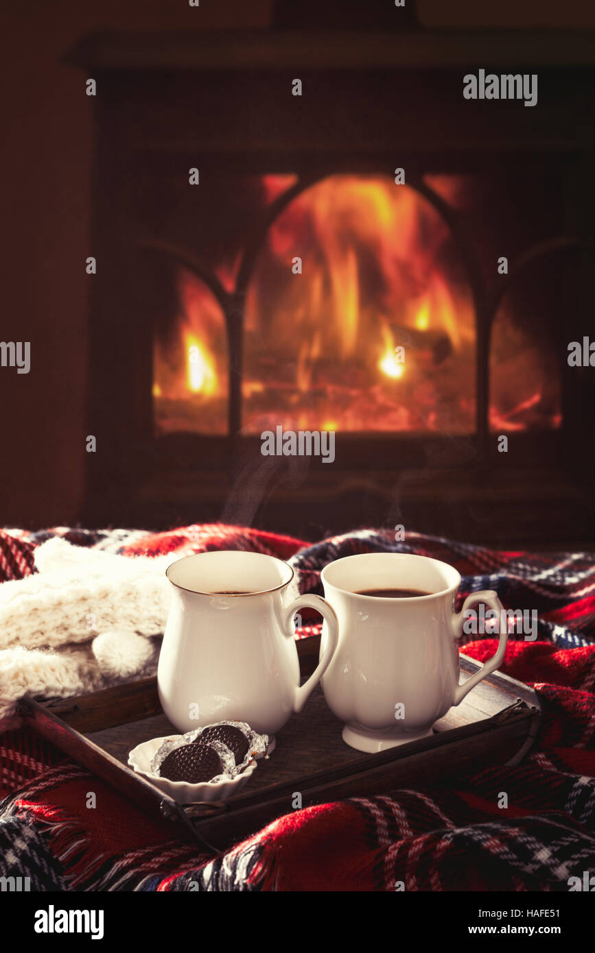 Warming drinks by the fireside - Stock Image