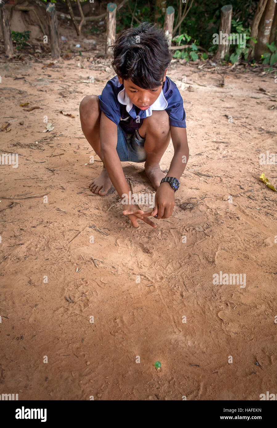 Young Cambodian village boy near Banteay Srei, Cambodia plays marbles in the dirt. - Stock Image