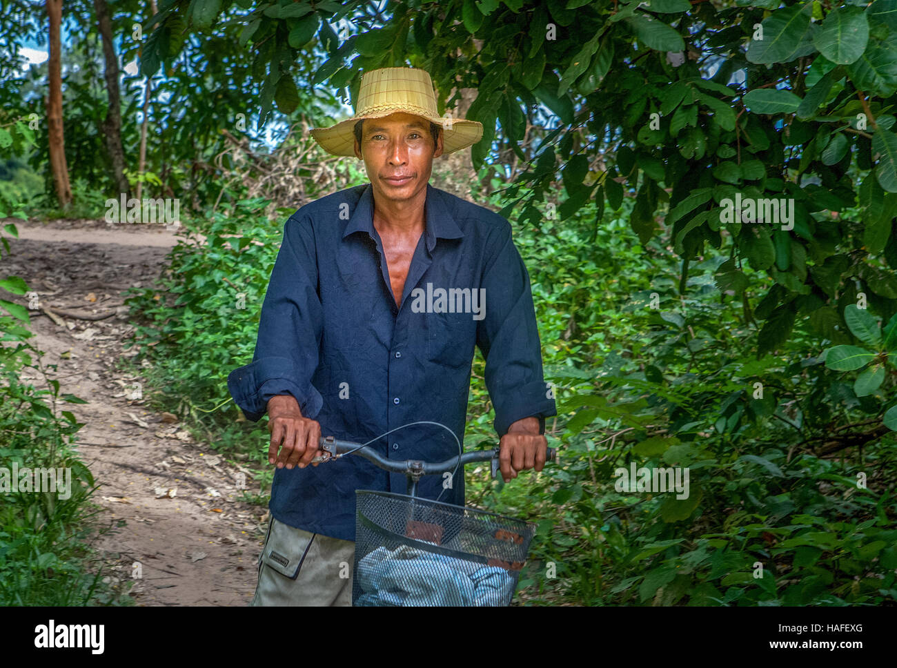 Portrait of a Cambodian Khmer rice farming man riding home on his bicycle in Banteay Srei, Kingdom of Cambodia. - Stock Image