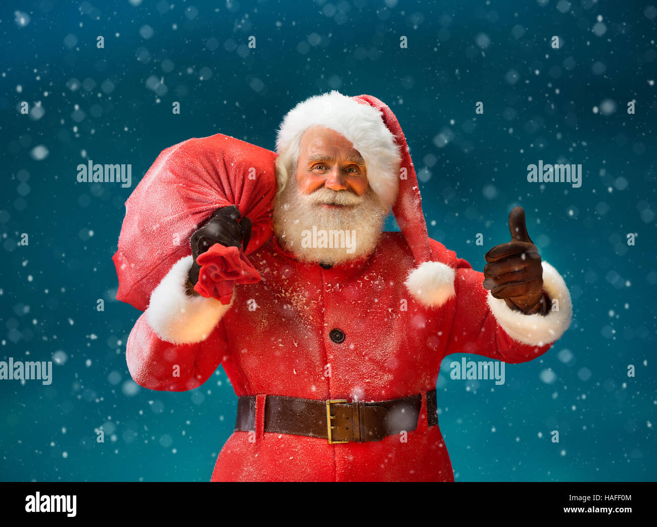 3148bf64cf0fd Happy Santa Claus gesturing thumb up with big bag full of gifts to  children. Merry Christmas   New Year s Eve concept.