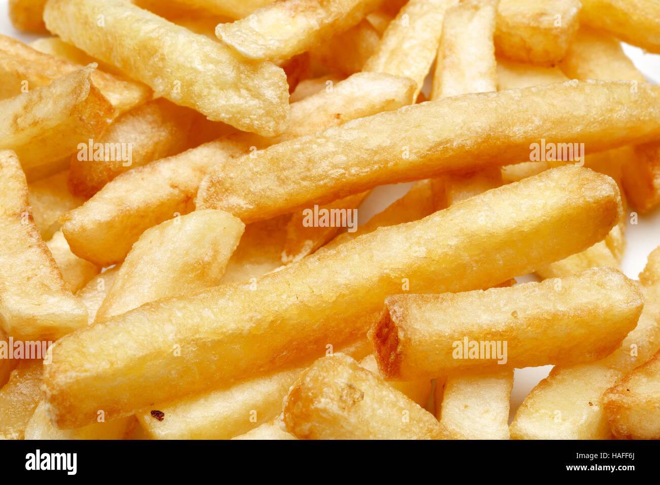 A pile of appetizing french fries on a white background. - Stock Image