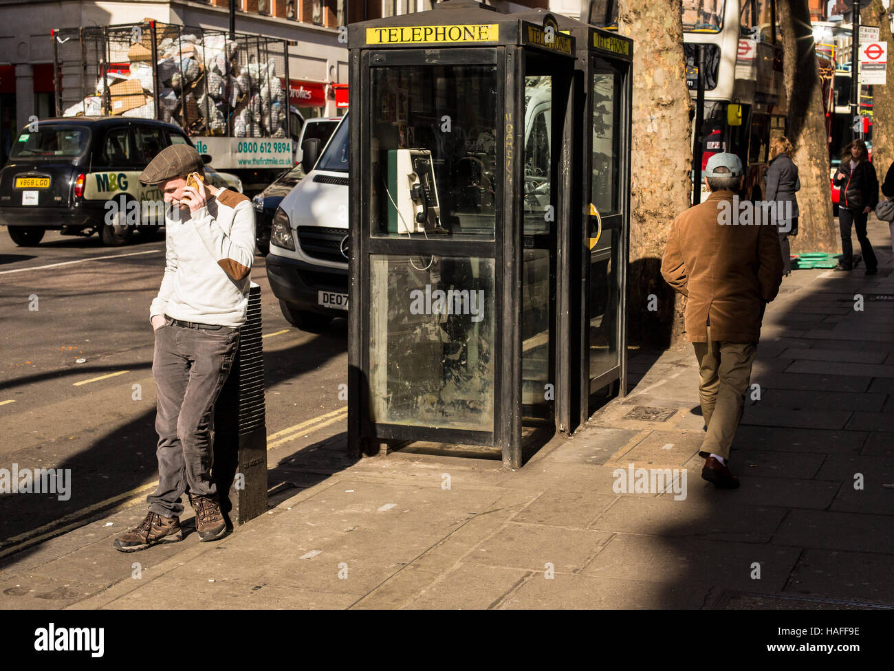 young man uses mobile phone near old style telephone box in London street - Stock Image