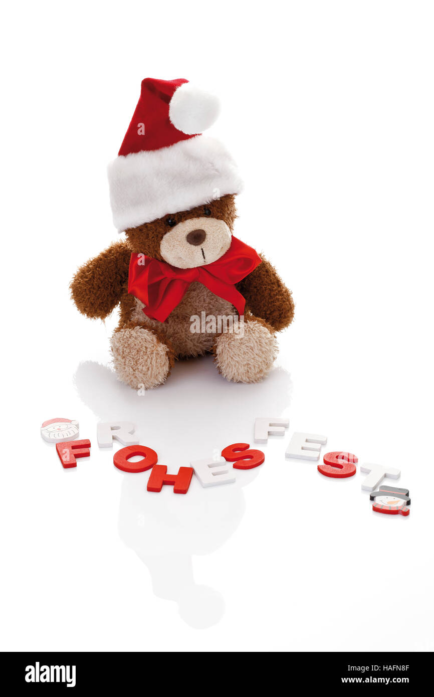Teddy bear with a Christmas hat and the writing 'Frohes Fest' (Happy Holidays) - Stock Image