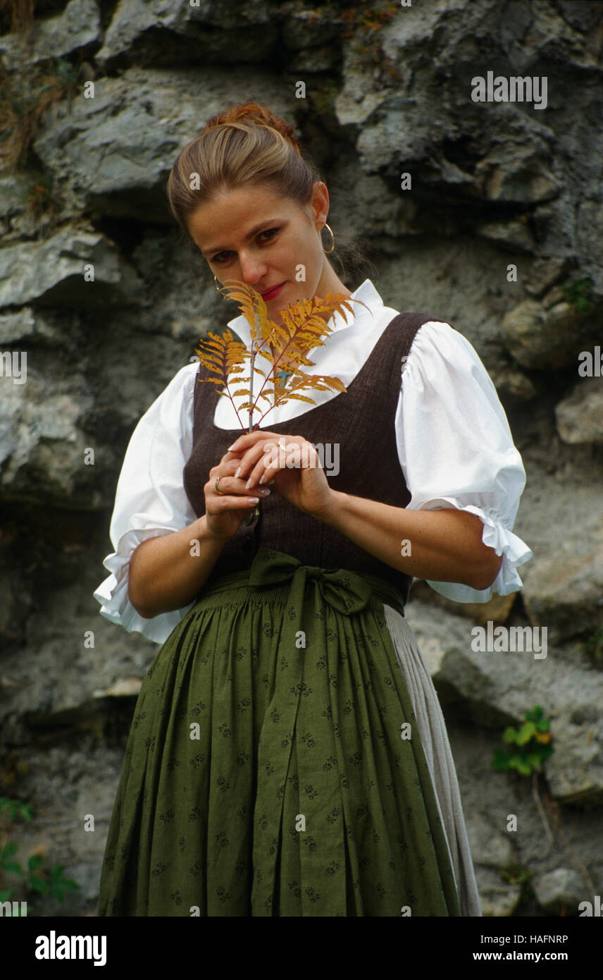 Woman, 30 year-old, wearing traditional dress of the town of Reichraming, posing in front of a rock face, Austria, - Stock Image