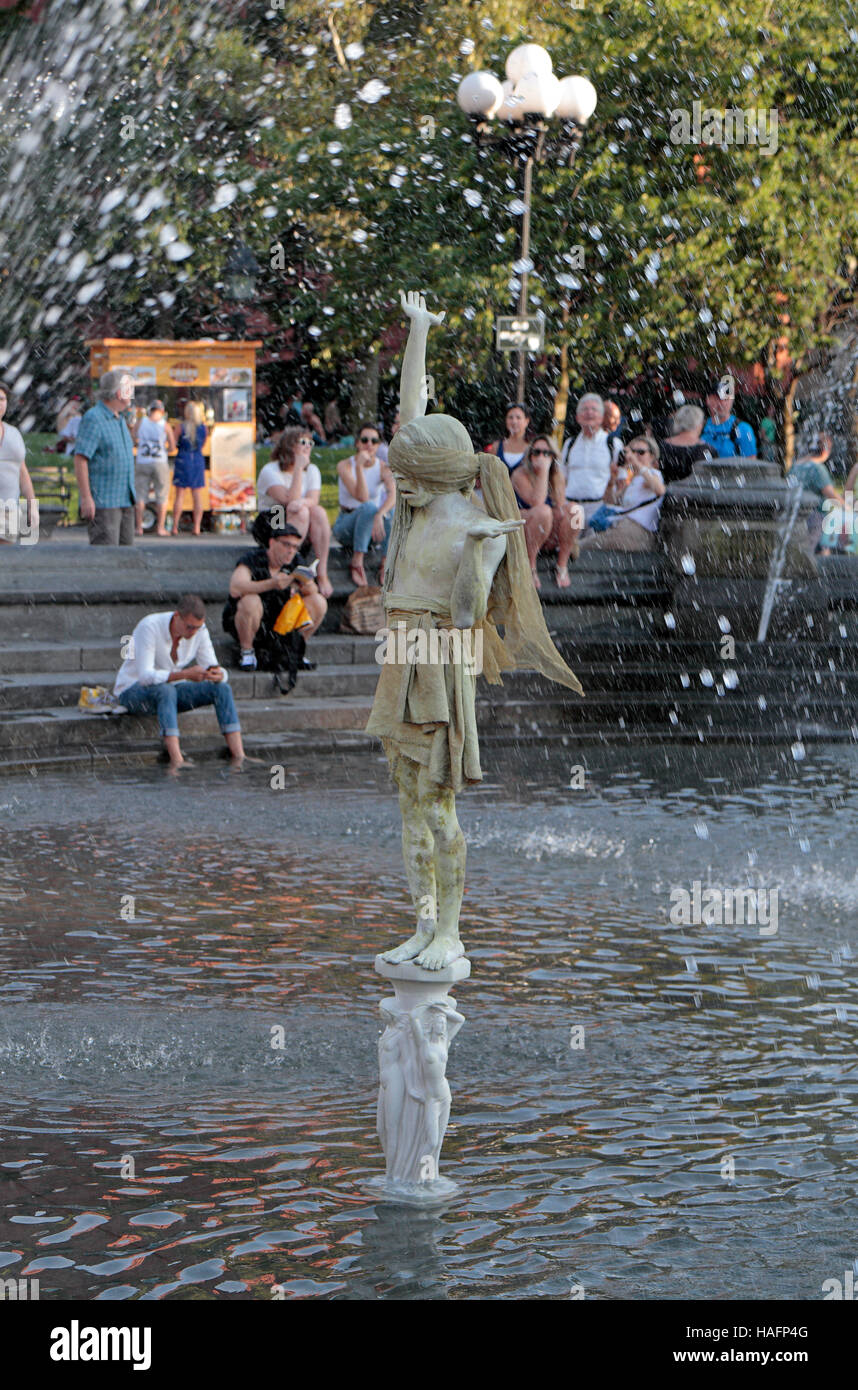 A street mime/statue artist standing in the fountain in Washington Square Park, New York City, United States. - Stock Image