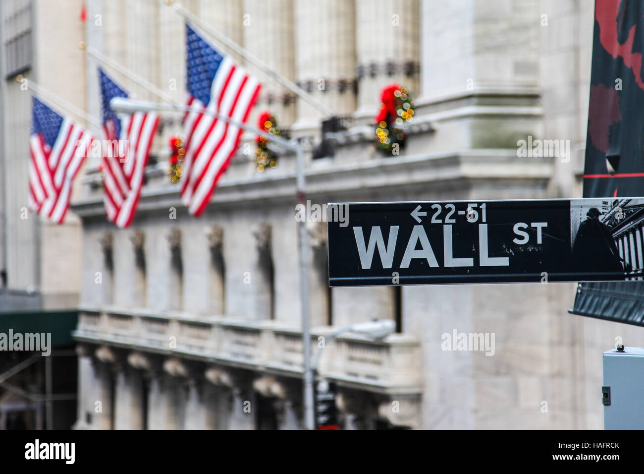 Wall Street  sign with American flag  and with New York Stock Exchange USA seen in New York - Stock Image