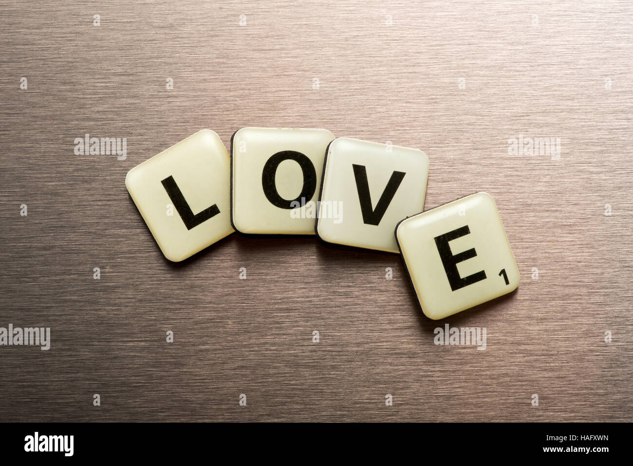 Word Love on letter blocks arranged in a curve on a textured metal surface with gradient lighting - Stock Image