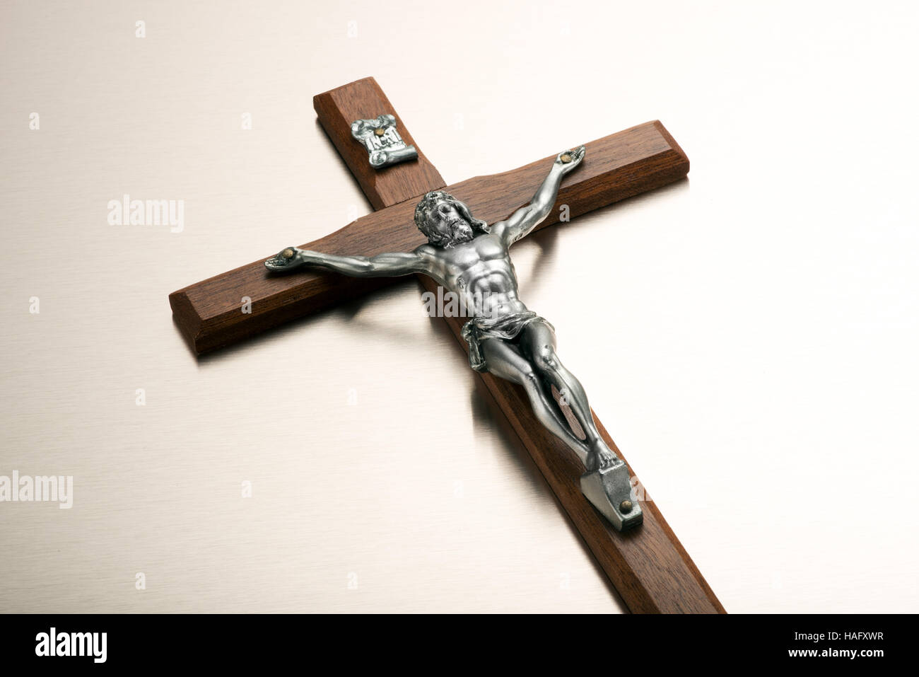 Silver metal figure of the crucified Christ on a wooden crucifix viewed low angle on white with copy space for Easter - Stock Image