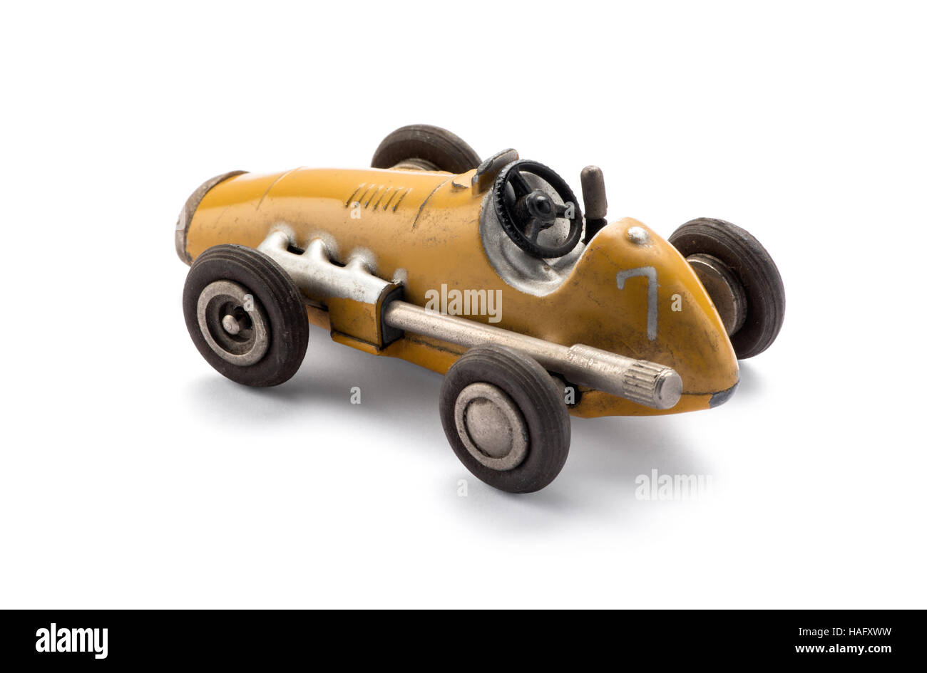 Model yellow toy vintage racing car in a side view showing the large exhaust over a white background with shadow - Stock Image