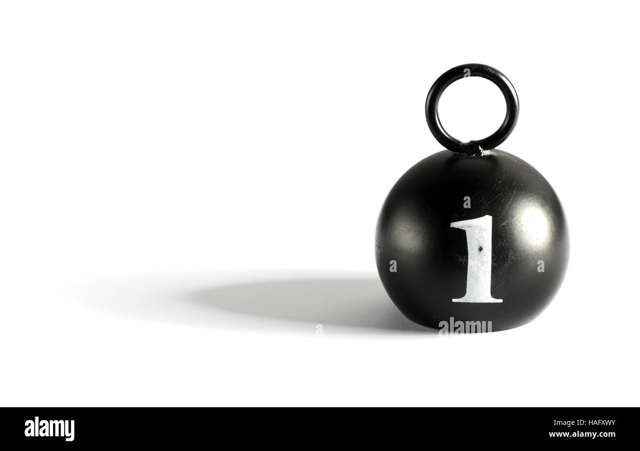 Old round black 1 kilogram counterpoise weight with handle on a white background with copy space and shadow - Stock Image