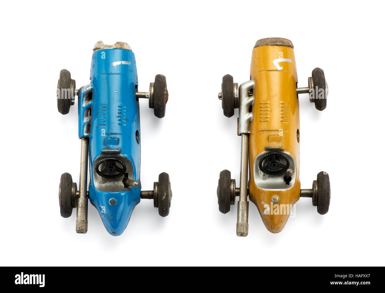 View from the top of two model vintage toy racing cars side by side in yellow and blue isolated on white - Stock Image