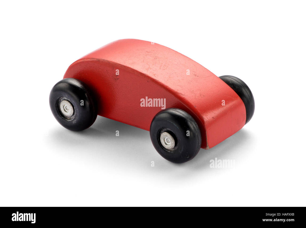 Simple stylized red wooden toy car with a curved design on large wheels in a high angle side view on white - Stock Image
