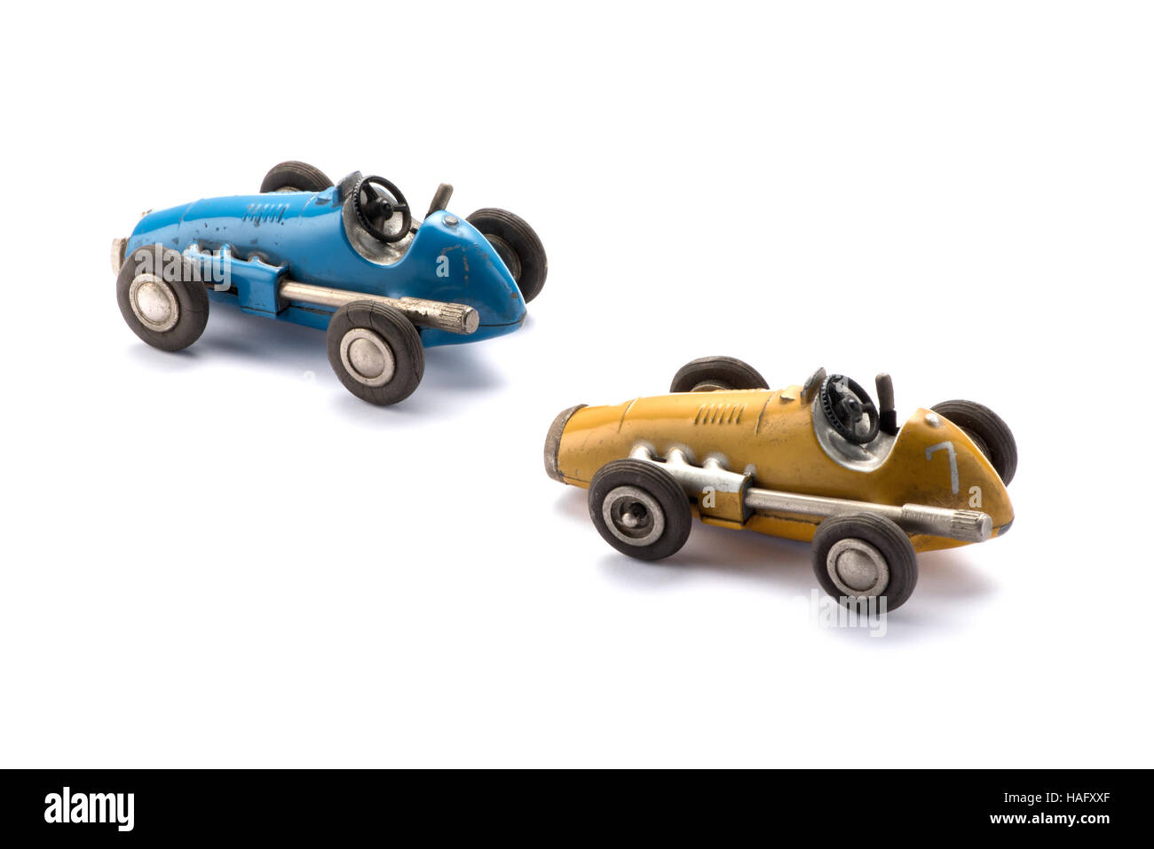 Two vintage style model toy racing cars in blue and yellow Stock Photo