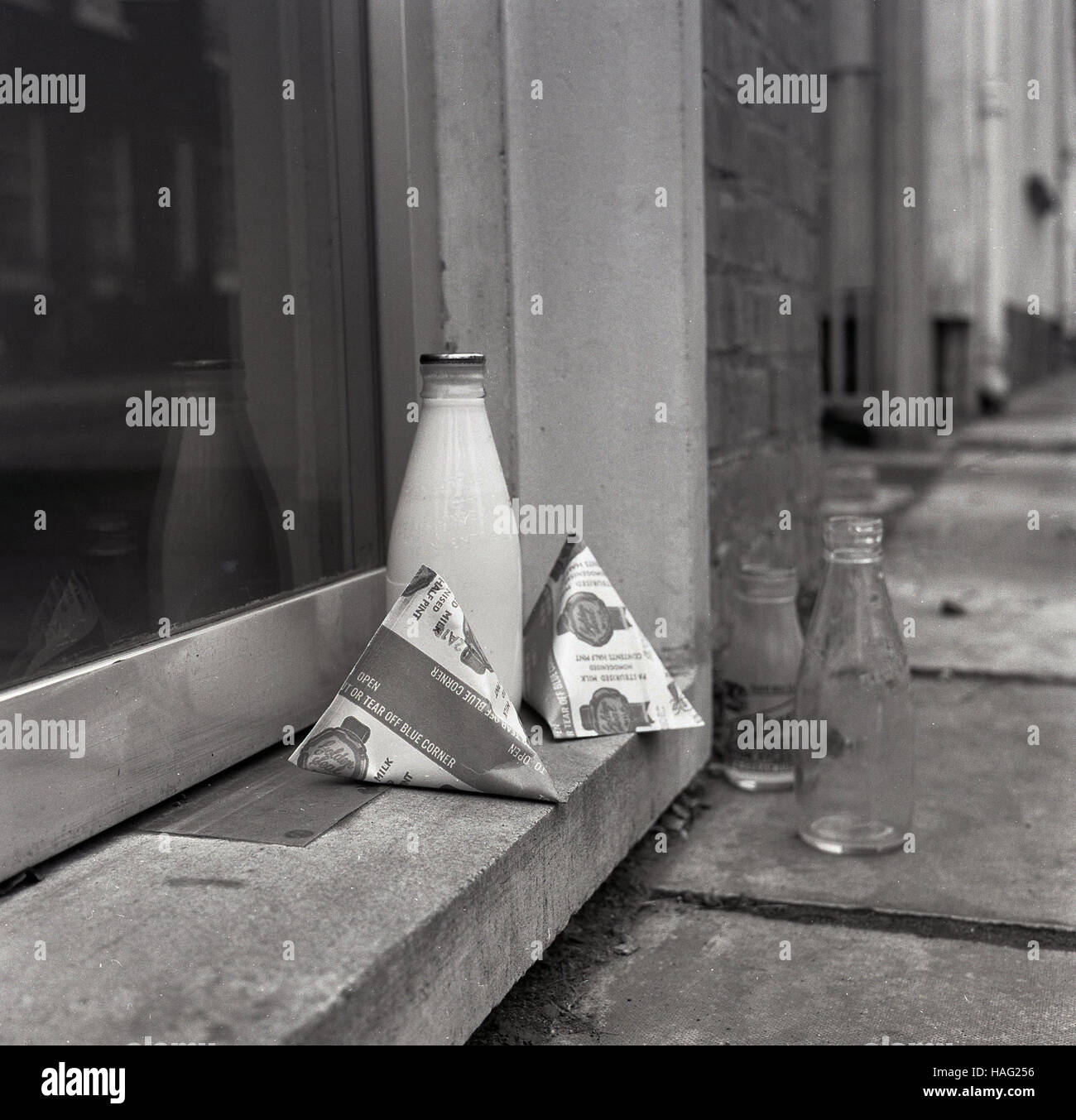 1965, historical, a pint size glass milk bottle and  two milk cartons sit on a house doorstep, with one empty glass - Stock Image