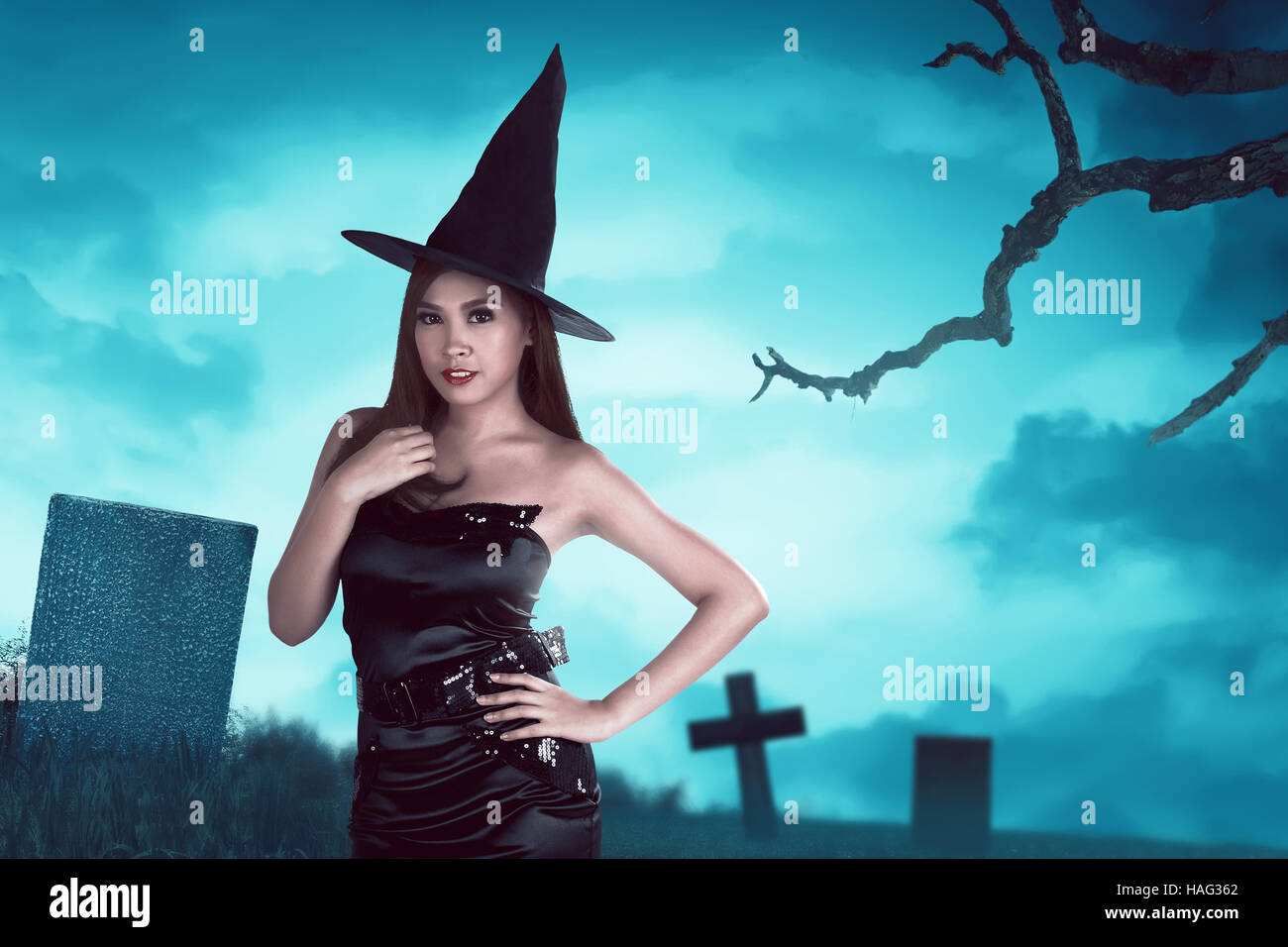 Young asian witch woman with hat standing around in a cemetery at night with moonlight Stock Photo