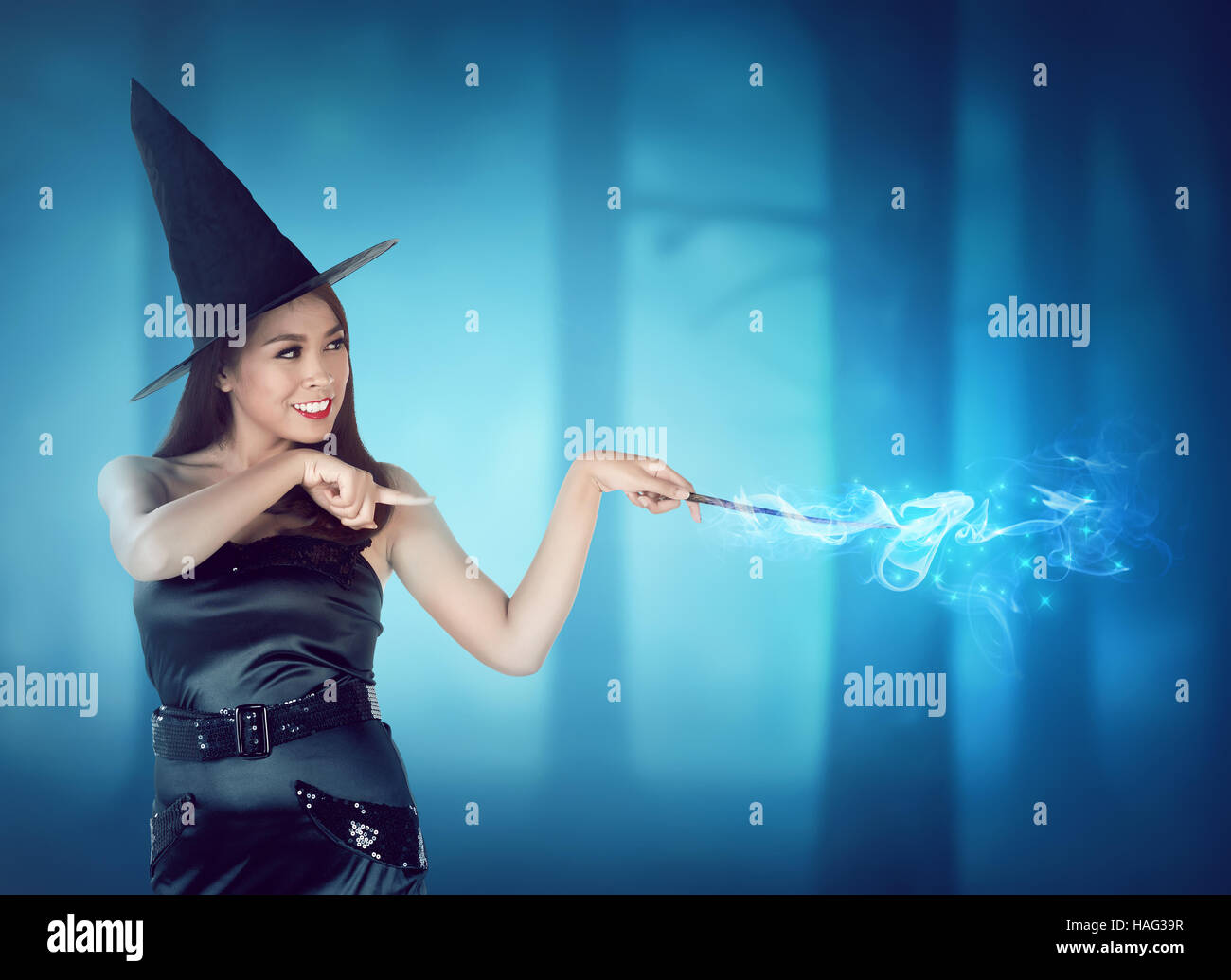 Beautiful young witch pointing and conjure something in the forest at midnight - Stock Image