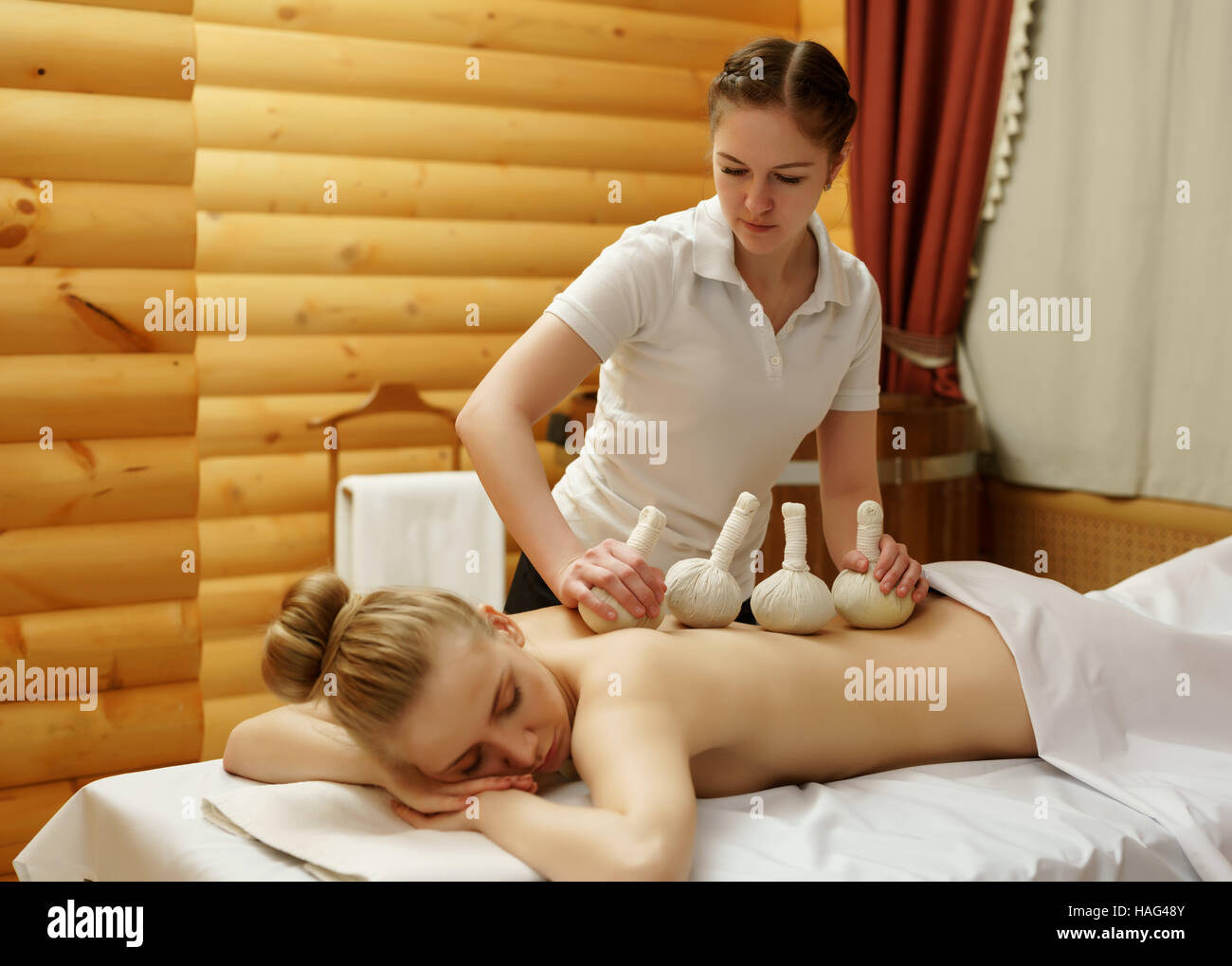 In spa. Masseuse puts salt bags on girl's back Stock Photo