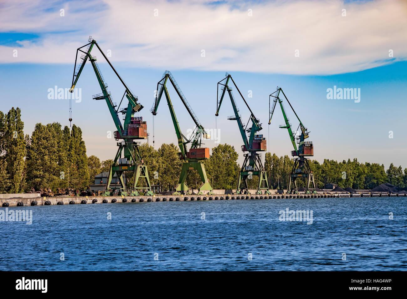 Port cranes for unloading sand on ship. Stock Photo