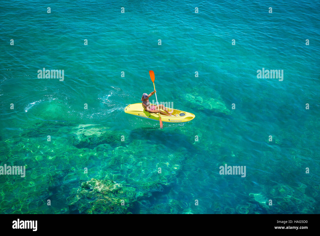 Man canoe sea, view of a man paddling a small yellow canoe across the harbour in Ortigia, Sicily. - Stock Image