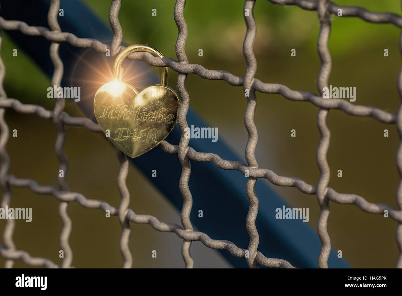 Heart shaped love padlock on a bridge. The padlock contains 'Ich liebe dich'.Valentine's day background. - Stock Image