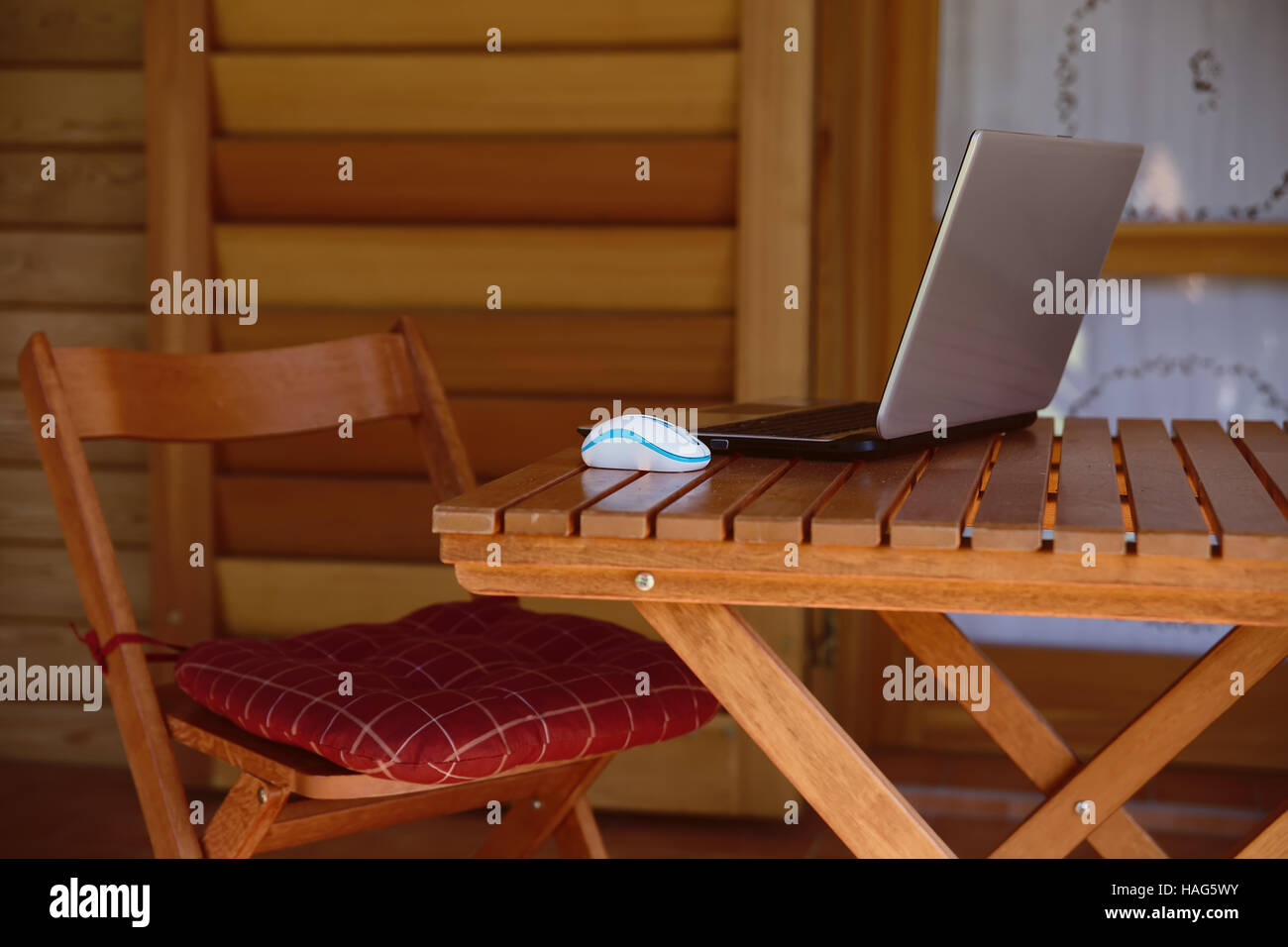 nomad work concept image with computer on wood table and sunlight, blurred trees of nature park background and summer - Stock Image