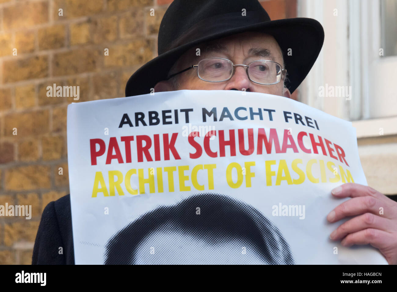 London, UK. 30th November 2016.  Ian Bone of Class War holds a poster showing Zaha Hadid Architects director Patrik - Stock Image
