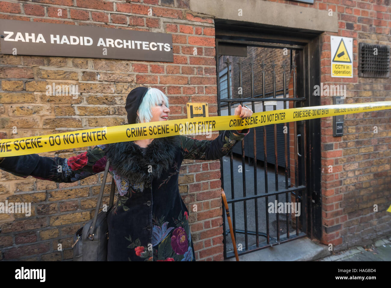 London, UK. 30th November 2016.  Jane Nicholl of Class War holds Crime Scene tape across the entrance to the London - Stock Image