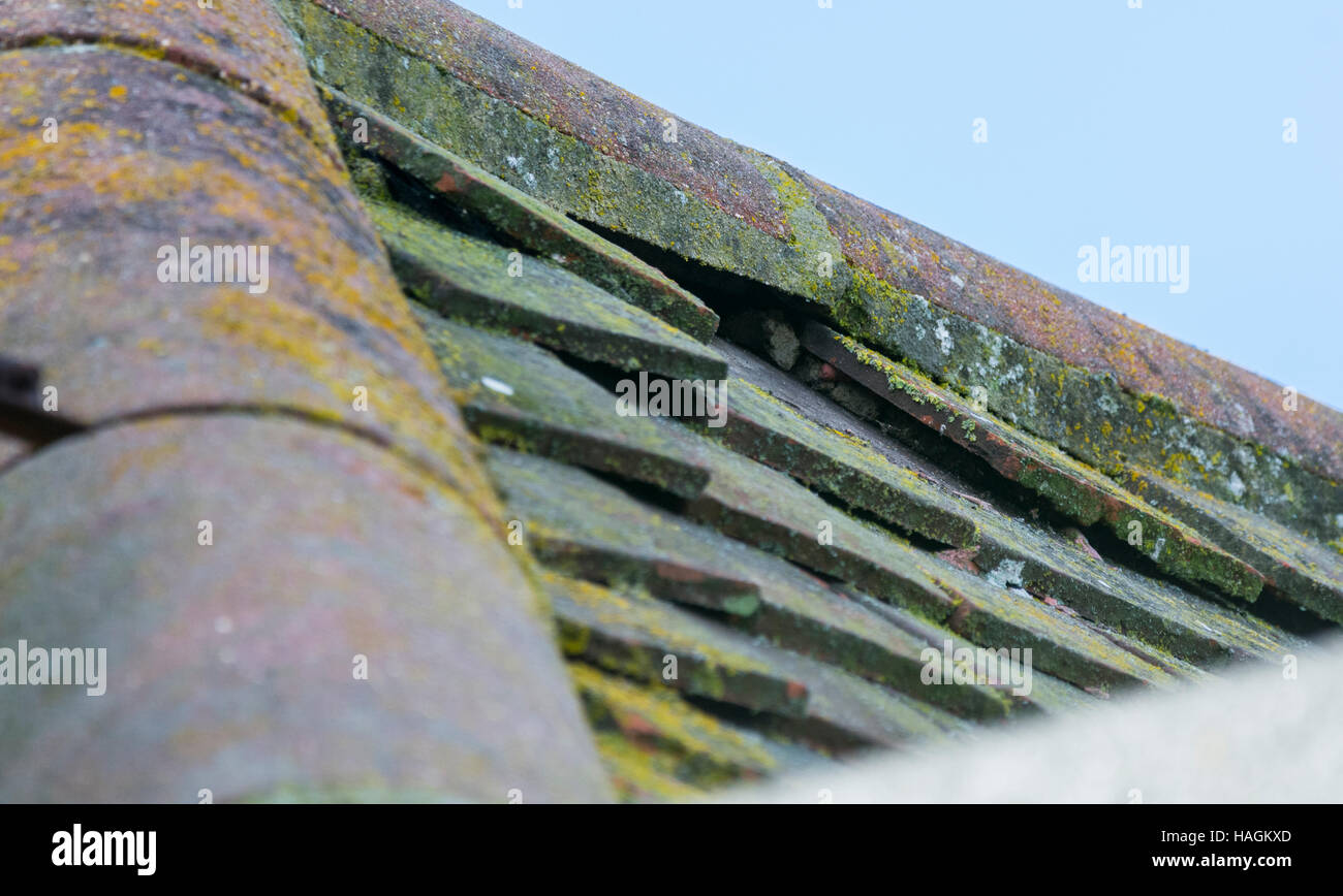 Missing tile on the roof of a house after a windy night. - Stock Image