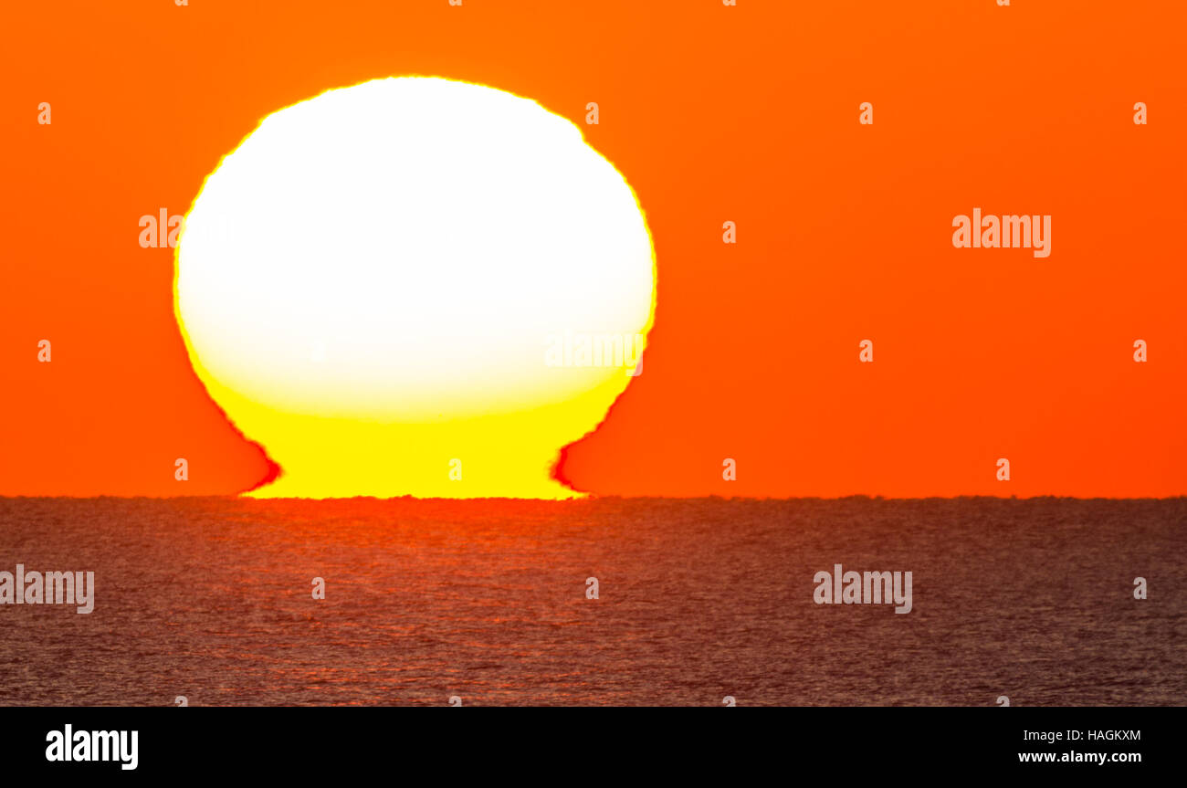 Sun setting over the sea. Sunset over the ocean. Sun dipping below the horizon. - Stock Image