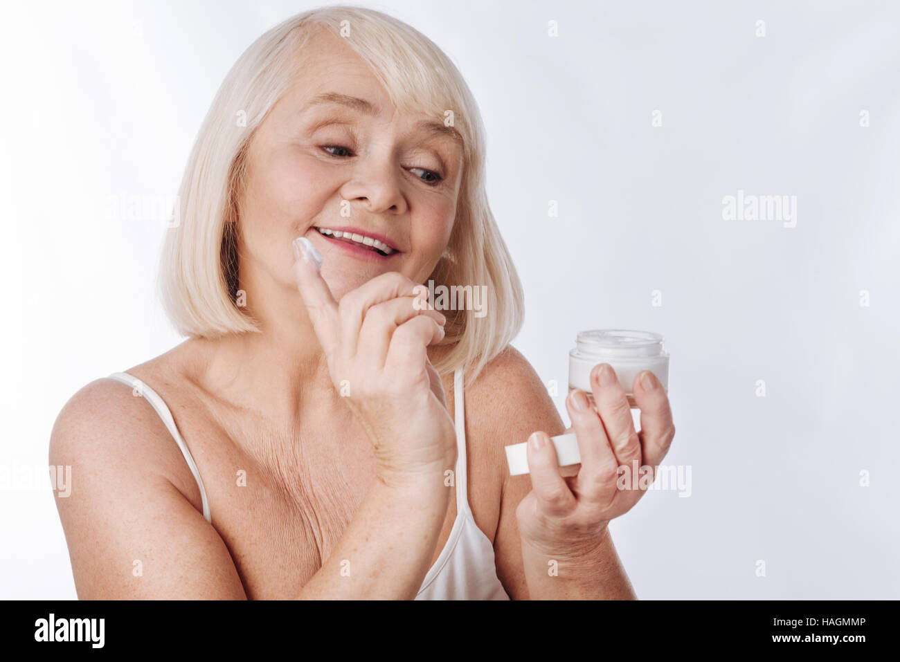 Nice good looking woman putting anti age cream - Stock Image