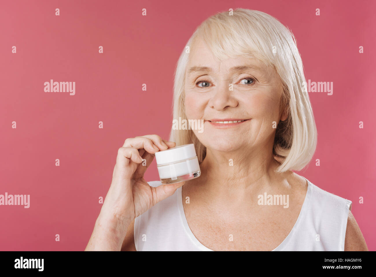 Positive elderly woman holding an anti age cream - Stock Image