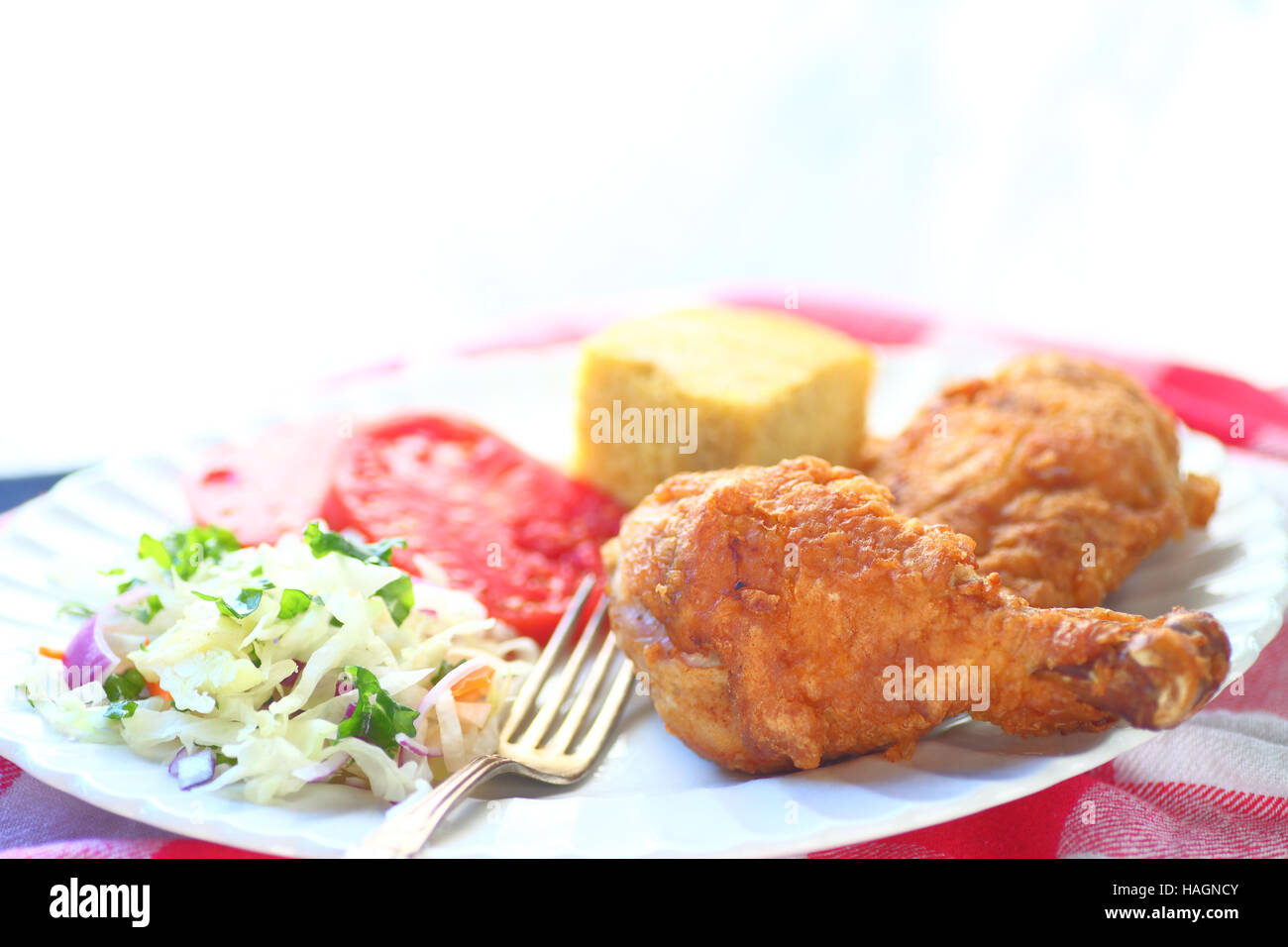 Fried chicken with coleslaw, tomatoes and cornbread with room for text - Stock Image