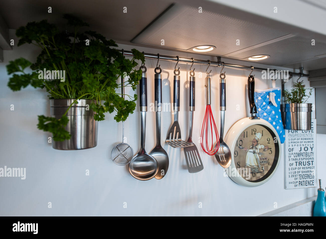 Various kitchen utensils hanging in a domestic kitchen. - Stock Image