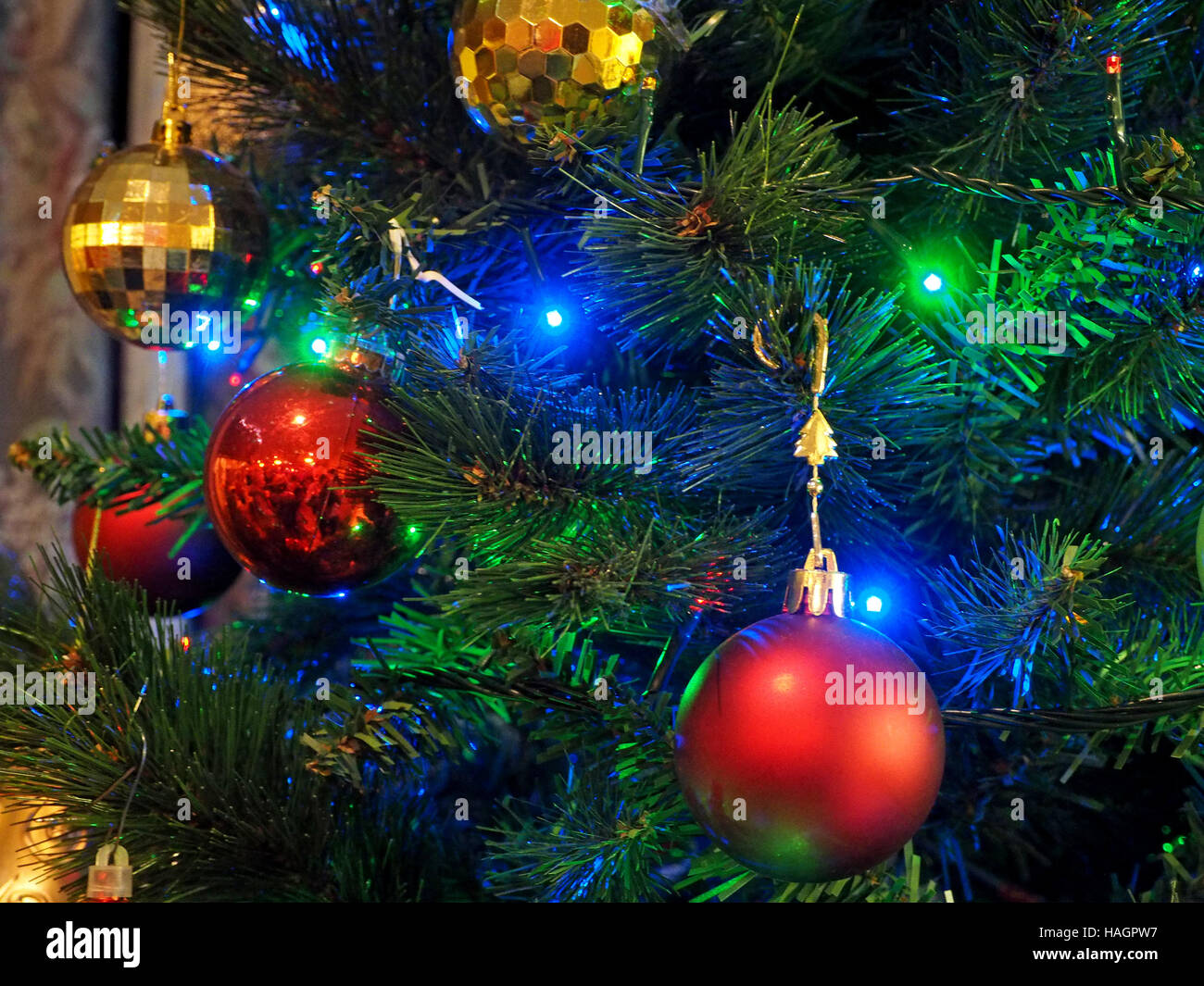 coloured colored lights on seasonal christmas decorations give festive red green gold and blue glow