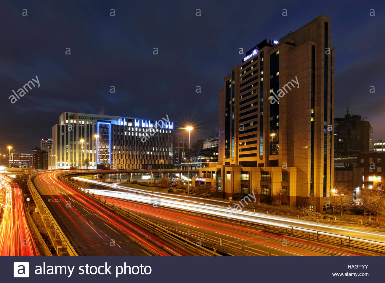 Car night trails heading to and from Glasgow city centre with the Hilton hotel and Scottish power buildings in view - Stock Image