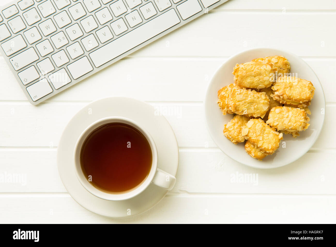 Break for tea and almond biscuits at the office. Concept with tea,cookies and computer keyboard. - Stock Image