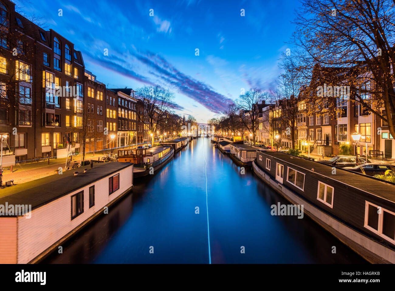Canal with House Boats in Amsterdam Netherlands - Stock Image