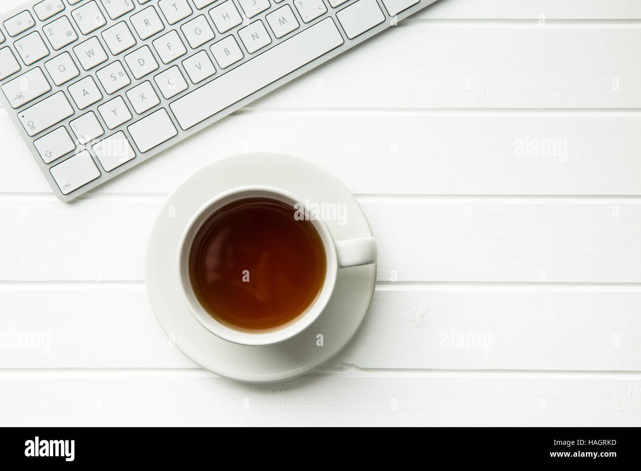 Cup of tea and computer keyboard on white table. Top view. - Stock Image