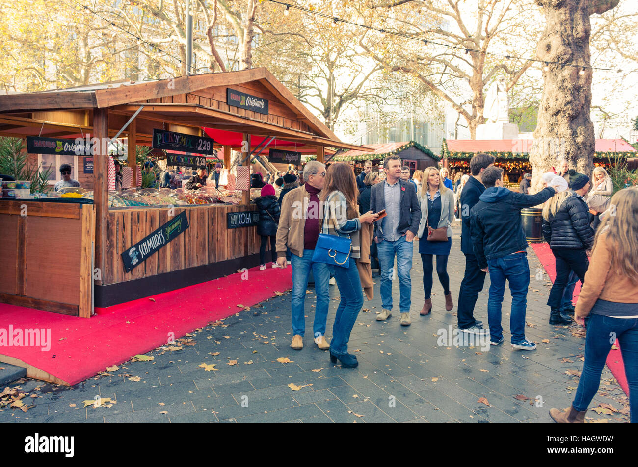 Visitors standing in front of the Bavarian style huts at the Christmas Market in Leicester Square, 2016, London, - Stock Image