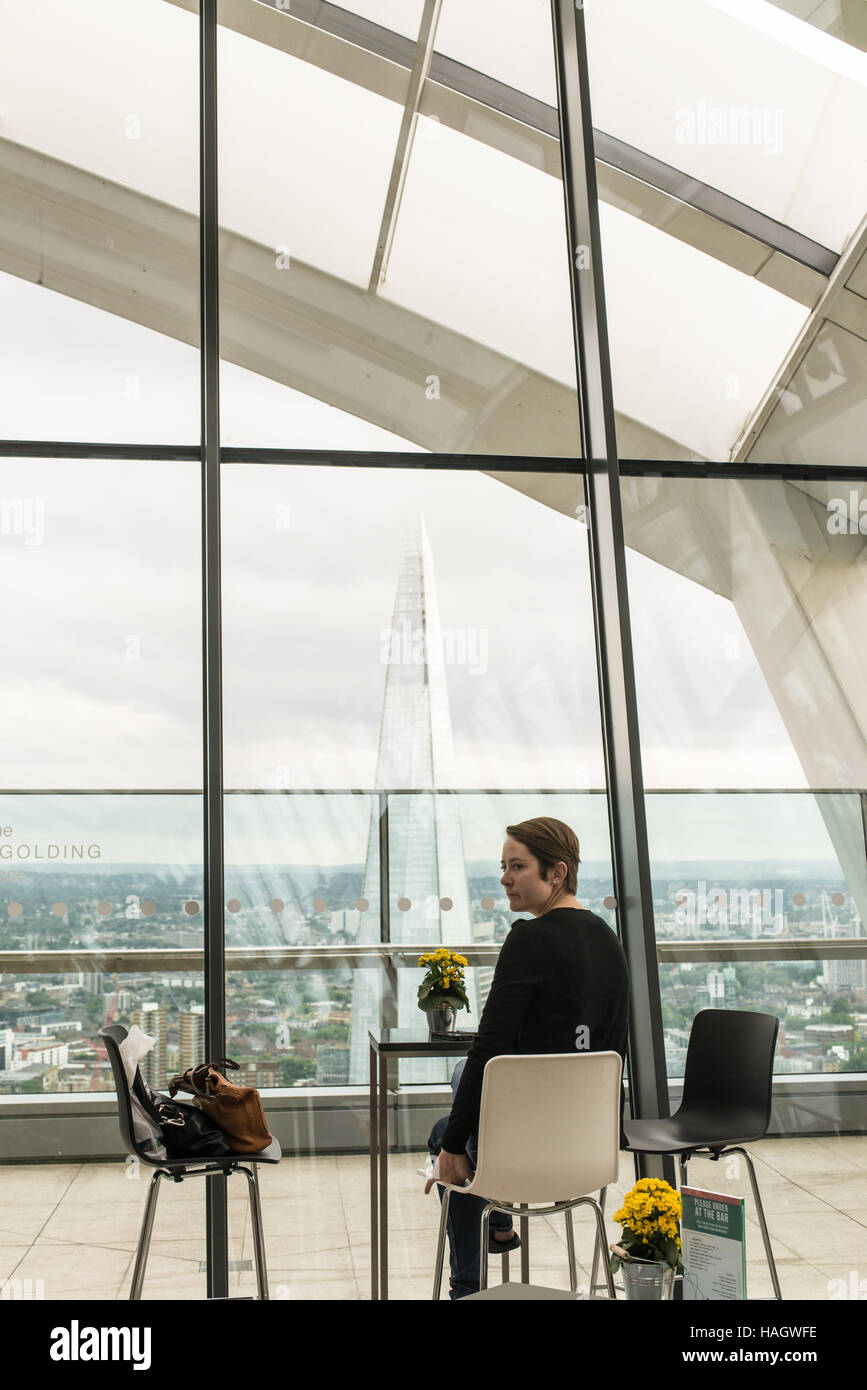Woman alone sitting at a table in a cool bar enjoying the spectacular view of the Shard from the Sky Garden - Stock Image