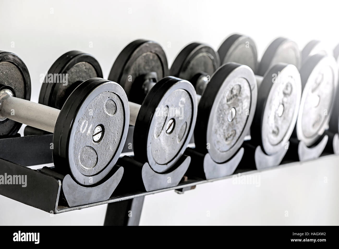 Sports dumbbells in  sports club. Weight Training Equipment,white background - Stock Image