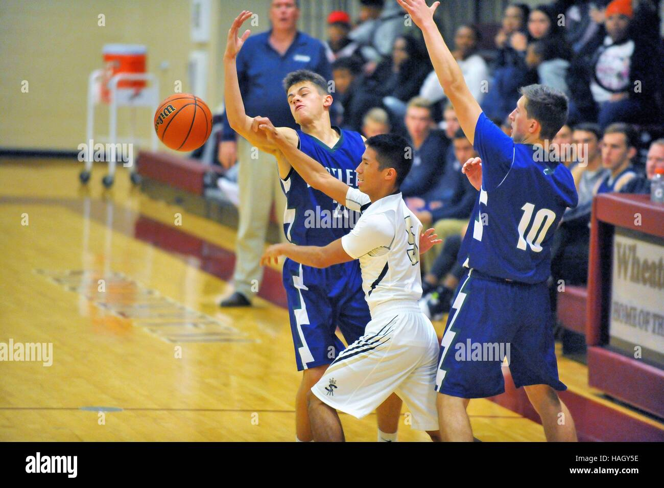 Players battle for possession of a loose ball along a sideline during a high school basketball game. USA. - Stock Image