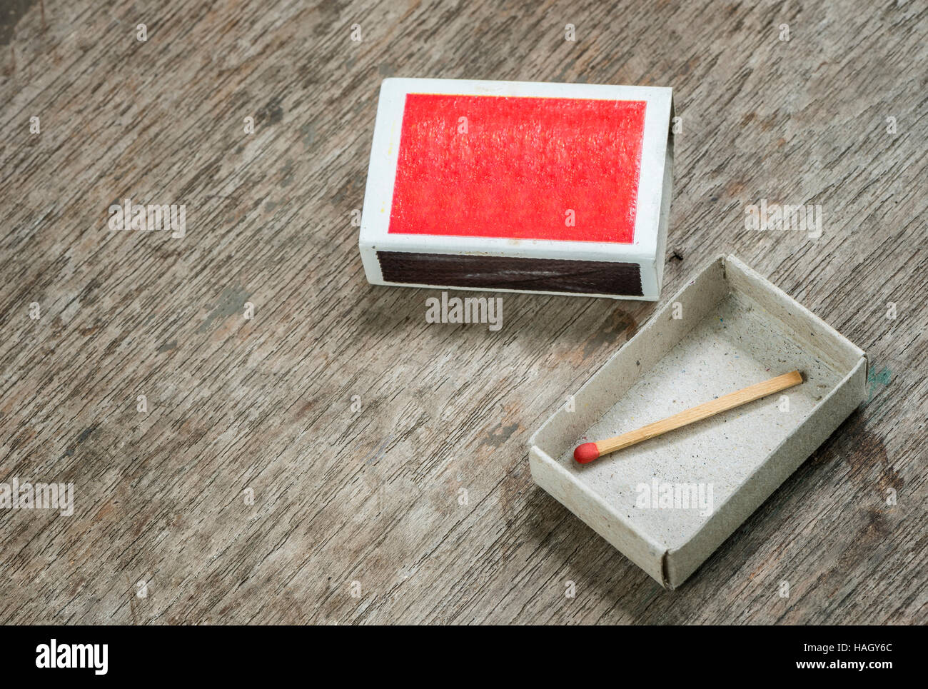 one match in the box on wooden background. - Stock Image